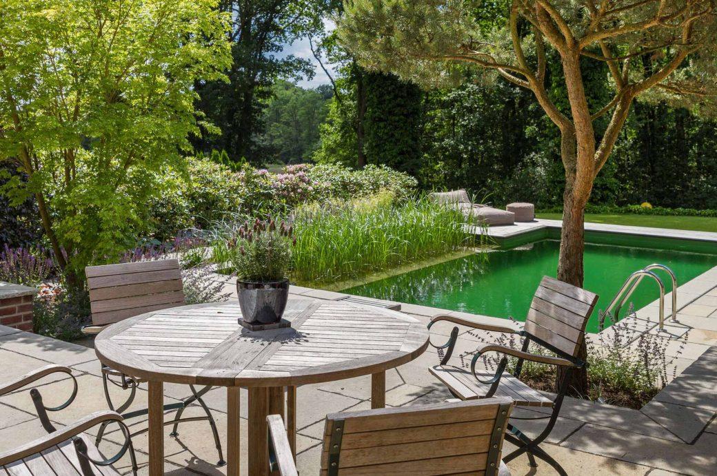 Tisch im Poolbereich eines von Beran Gärten und den International Tree Brokern gestalteten Privatgartens